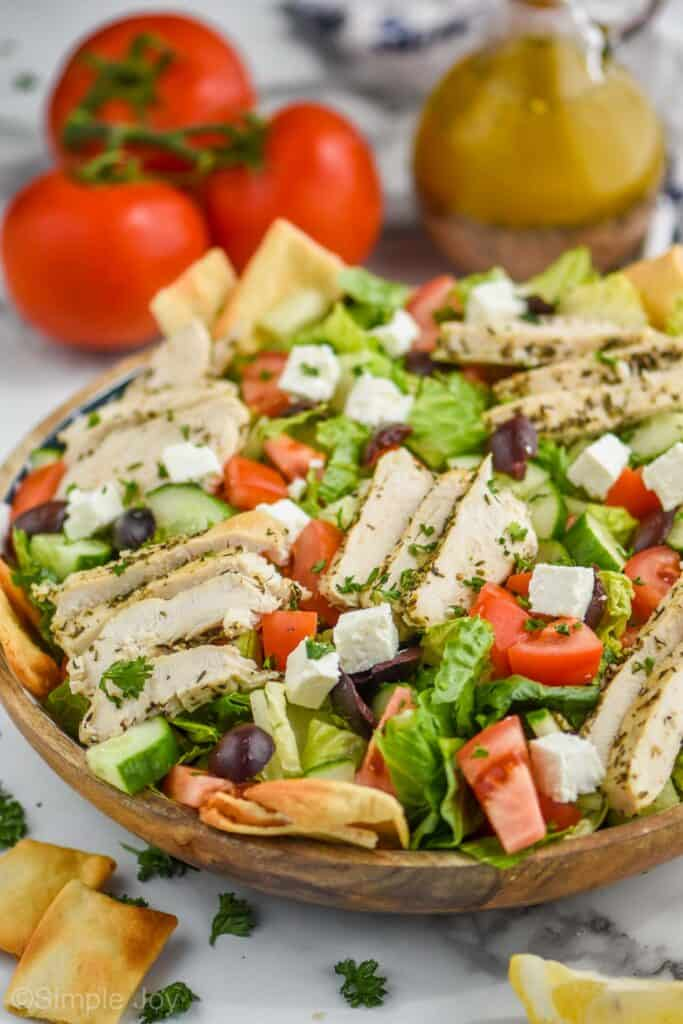 side view of a greek salad with chicken and served with pita chips