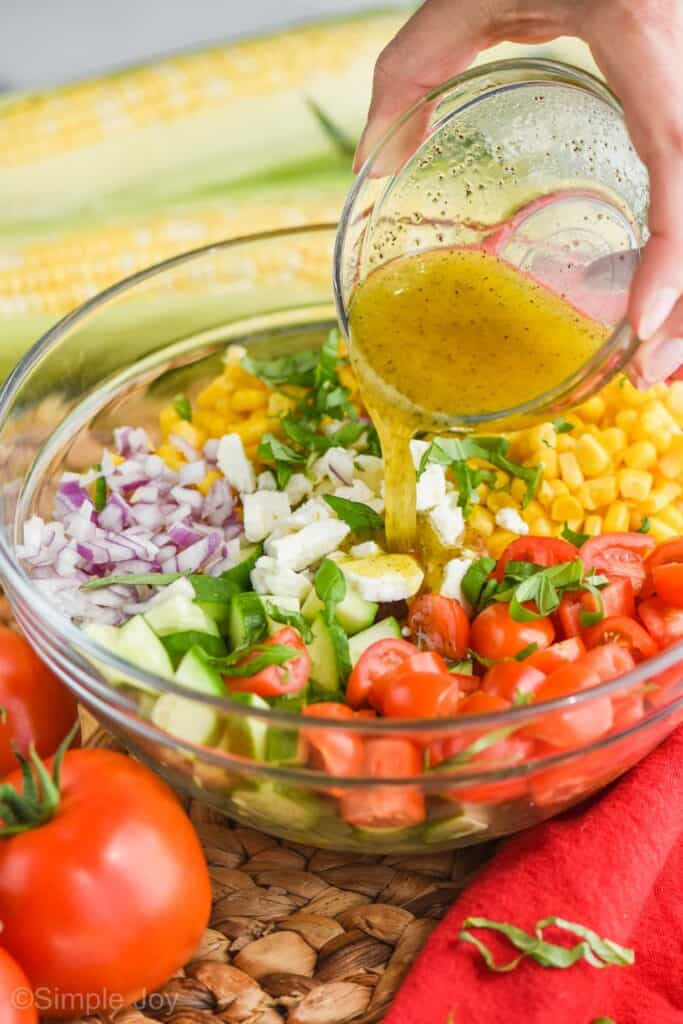 hand pouring dressing over summer corn salad in a glass bowl