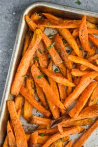 overhead photo of baked sweet potato fries on a baking sheet garnished with fresh parsley