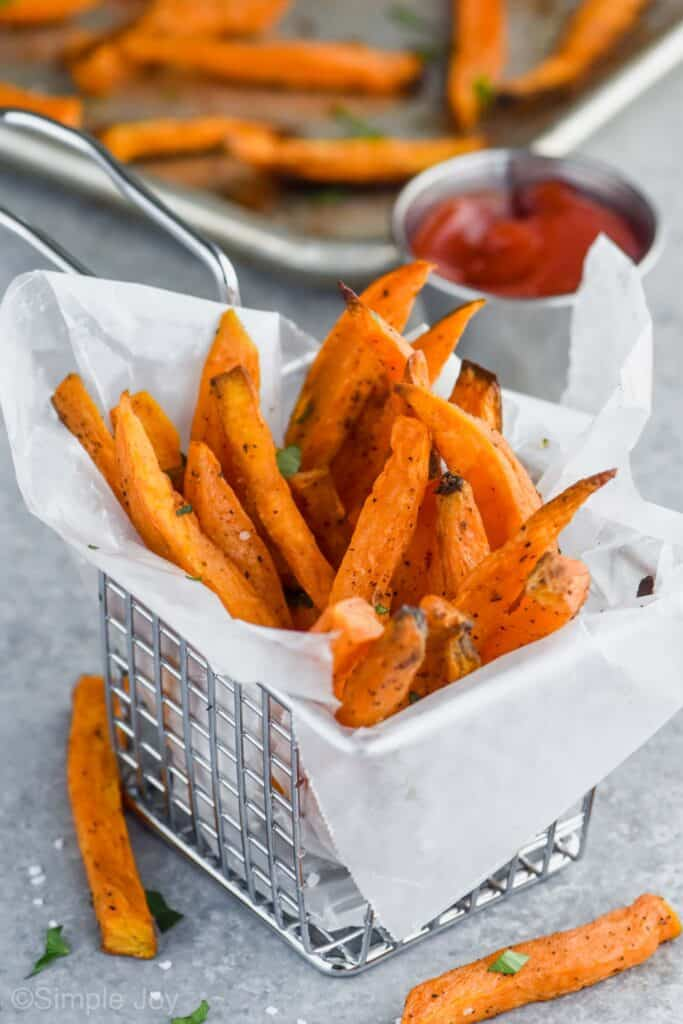 sweet potato fries in a wire basket that is lined with wax paper with a small cup of ketchup in the background