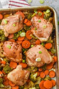 teriyaki chicken thighs on a baking sheet with broccoli, onions, and carrots, garnished with sesame seeds and green onions