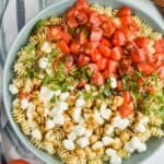 overhead view of a large bowl full of pearl mozzarella, pasta, fresh shredded basil, and quartered cherry tomatoes covered in balsamic dressing