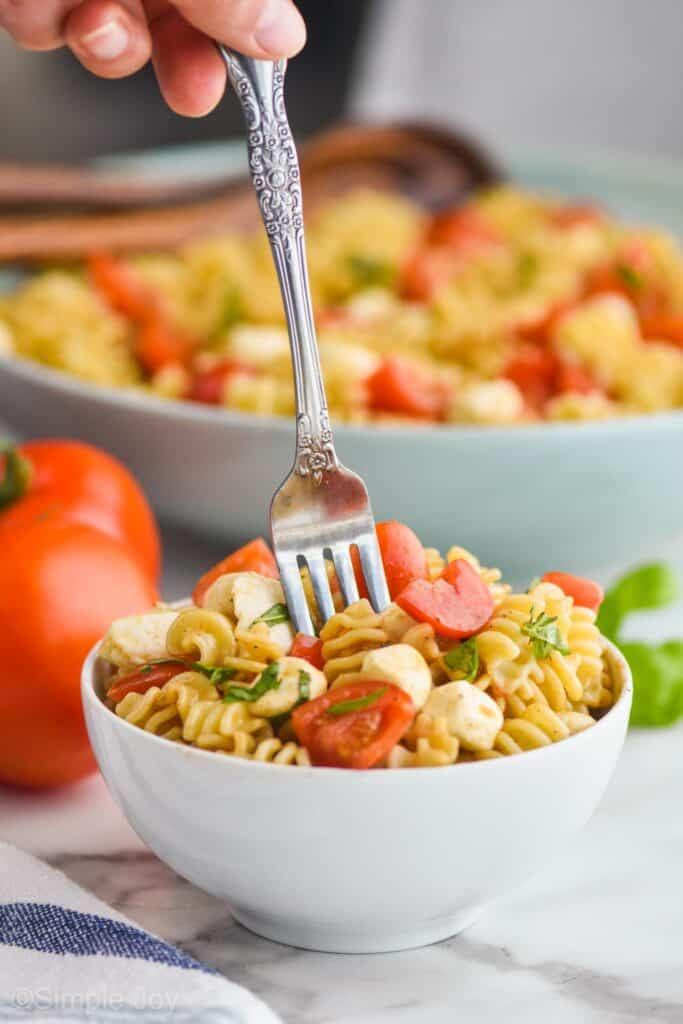 small white bowl full of caprese pasta salad with a fork digging into the middle