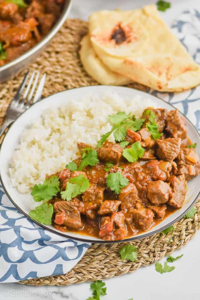 a plate with beef curry recipe on one side and and rice on the other side with naan bread in the background