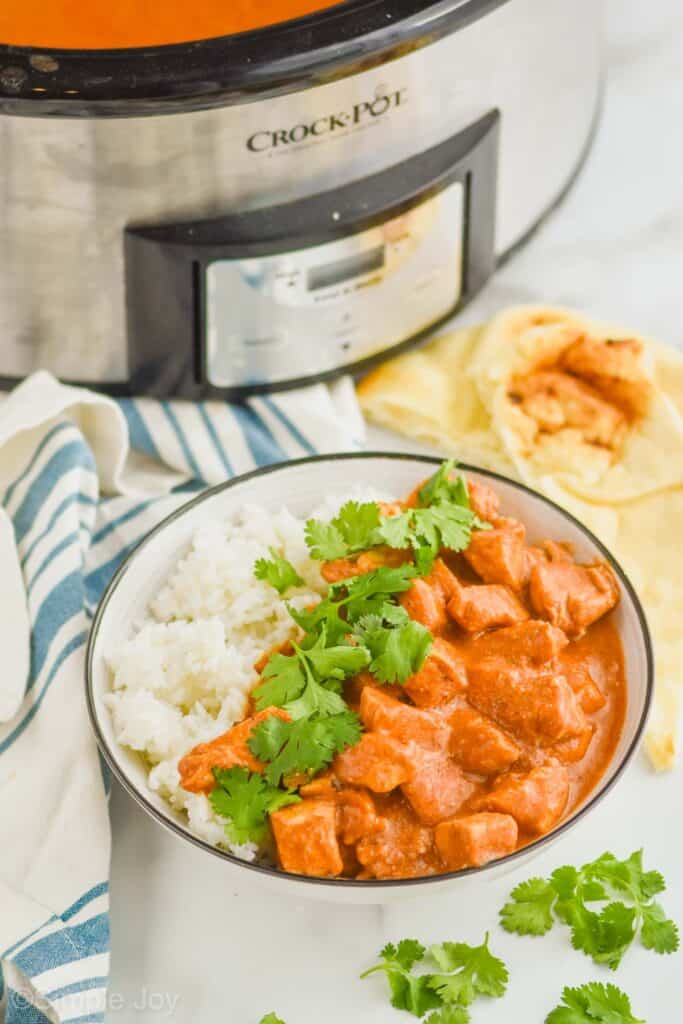 bowl of crockpot butter chicken with naan bread on the side and a slow cooker in the background
