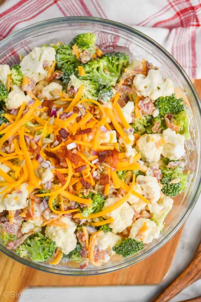 close up of broccoli cauliflower salad in a glass serving bowl with extra shredded cheddar cheese, bacon pieces, sunflower seeds, and diced red onions on top