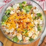 overhead view of broccoli cauliflower salad in a clear serving bowl with extra bacon, cheese, sunflower seeds and red onions on top