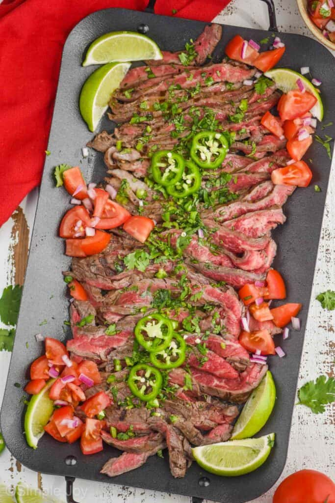 overhead view of cut up up carne asada on a platter with sliced jalapeños, diced tomatoes, sliced limes, and chopped cilantro