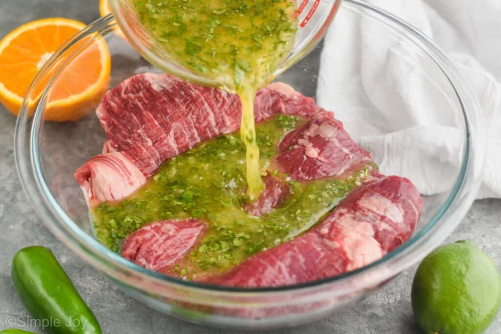 carne asada marinade being poured over skirt steak in a large glass mixing bowl