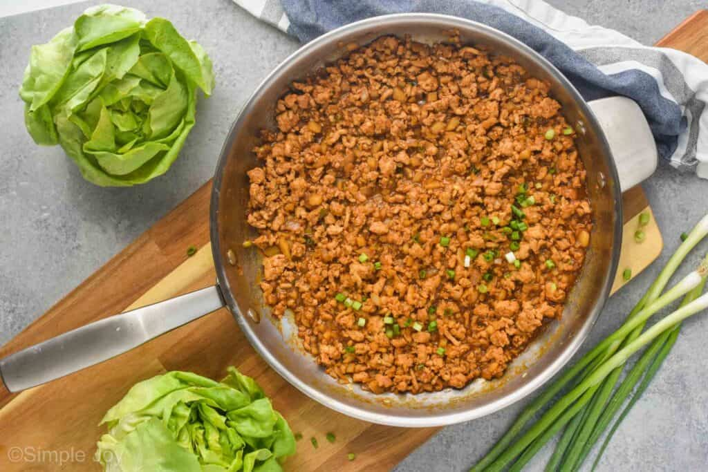 overhead of a pan on a cutting board holding the filling to chicken lettuce wraps with two heads of Bibb lettuce next to it