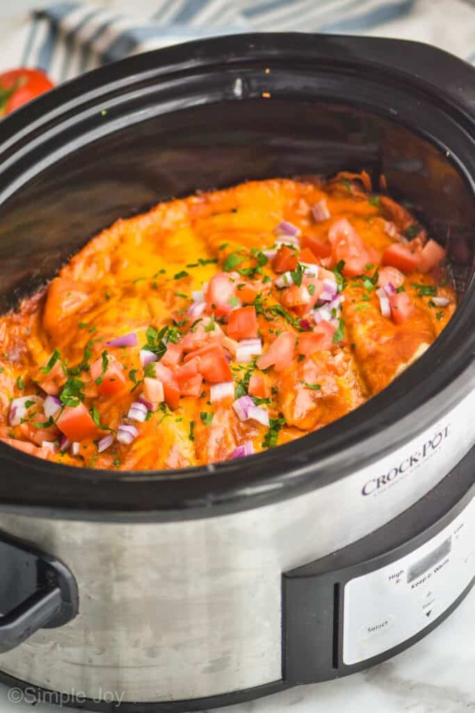side view of a crock pot holding chicken enchiladas garnished with diced red onion, cilantro, and tomatoes on top