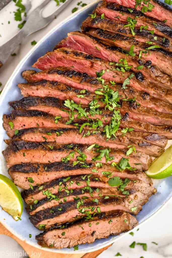 overhead of a grilled flank steak recipe on a platter with cilantro and lime wedges