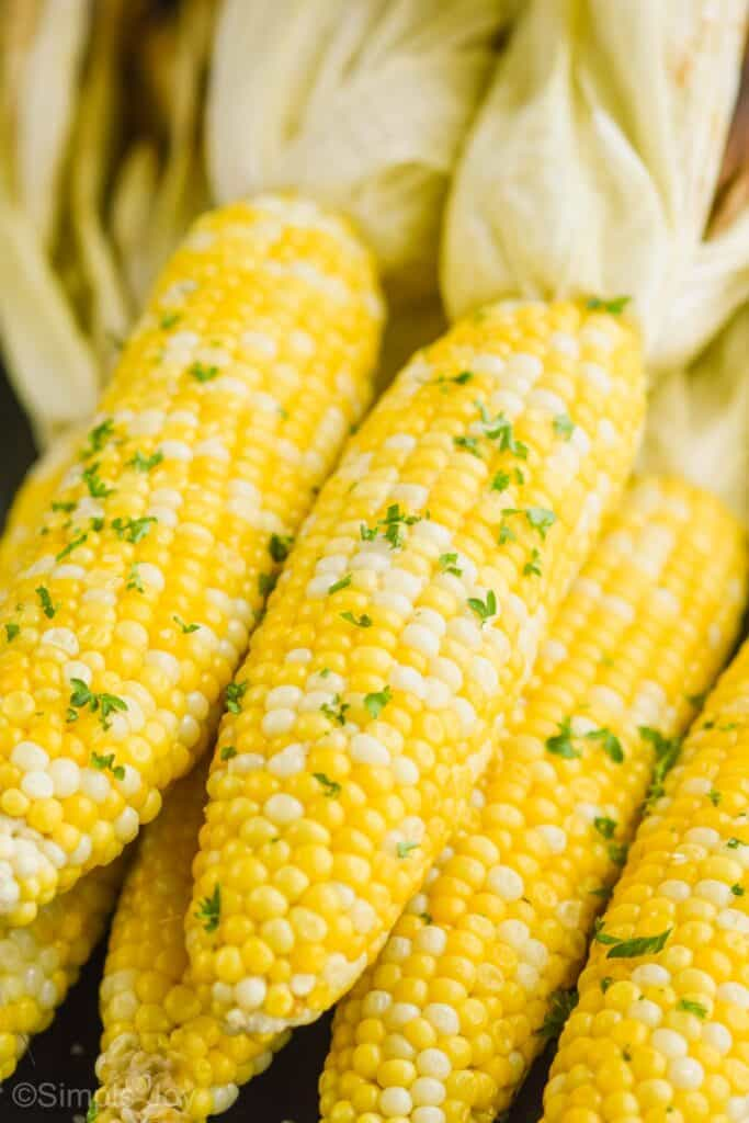 up close of fresh corn that has been grilled with  butter and fresh parsley