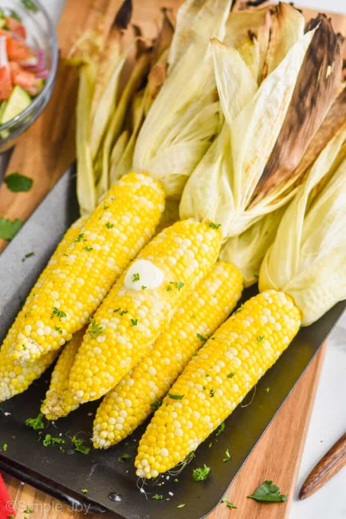 pulled back view of grilled corn on the cob with the husks pulled back that has butter on it and fresh parsley on a platter