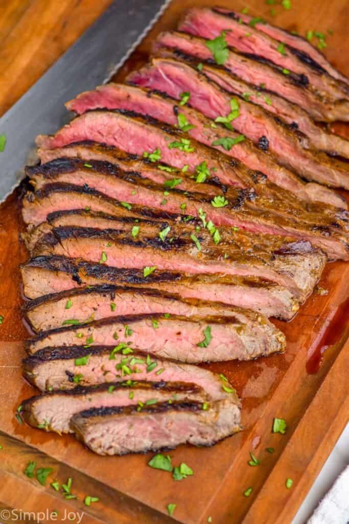 a grilled flank steak, sliced on a cutting board