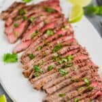 a grilled flank steak cooked and cut into thin slices with cilantro on top