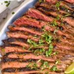 pinterest graphic of overhead of a grilled flank steak recipe on a platter with cilantro and lime wedges