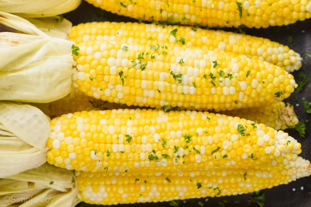 up close view of grilled corn that has had the husks pulled back with fresh parsley and butter
