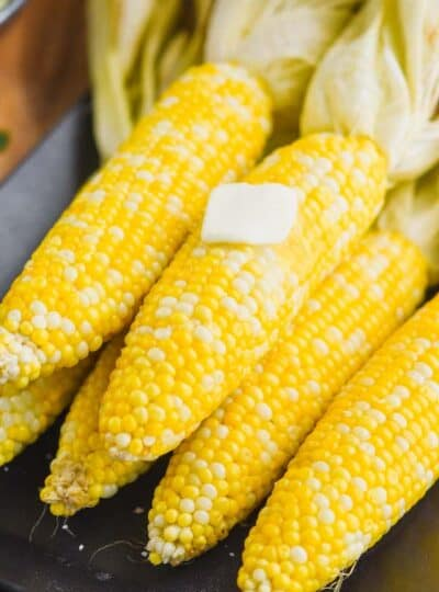 grilled corn with the husks pulled back and a square of butter melting on the cob