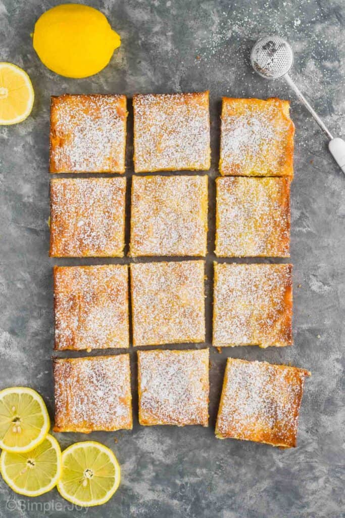 overhead of a full batch of lemon magic bars topped with powdered sugar cut into 12 squares