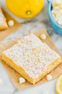 one lemon magic bar topped with powdered sugar on a square of parchment paper with white chocolate chips and lemons around