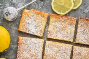 two rows of lemon magic bars from overhead with a powdered sugar wand and two lemon slices and a lemon next to them