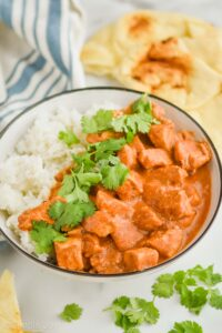 crockpot butter chicken recipe in a bowl with rice and garnished with fresh cilantro