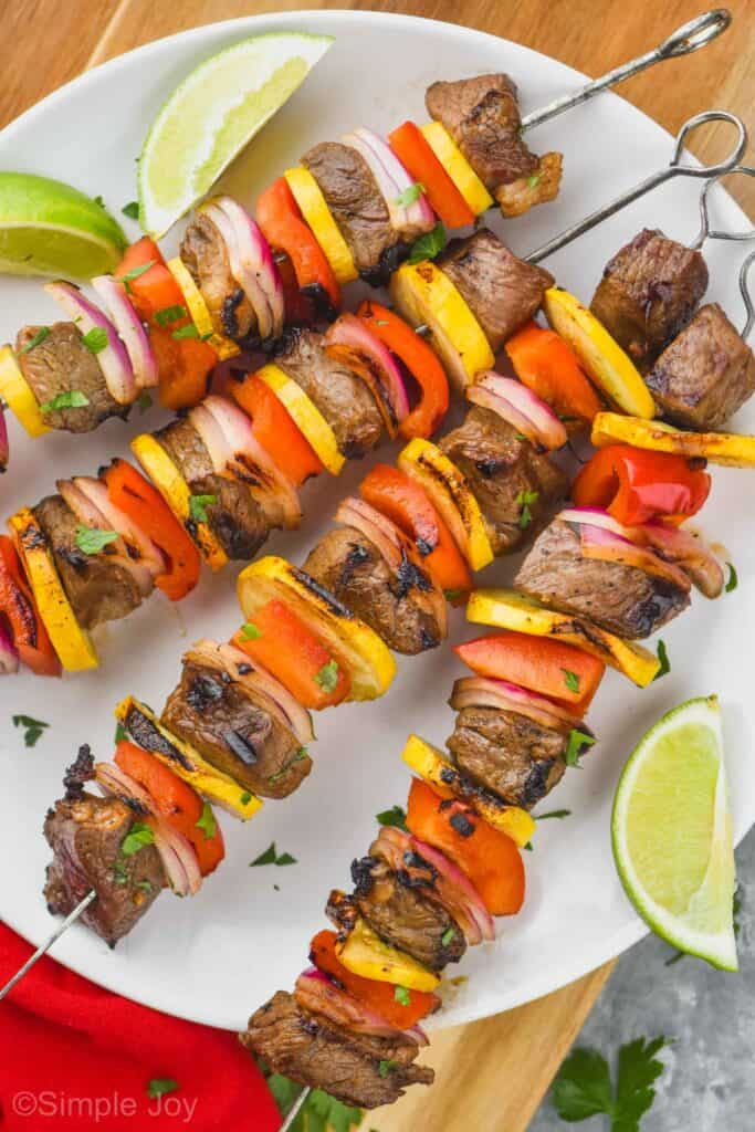 four steak kabobs on a white round plate with lime wedges around them