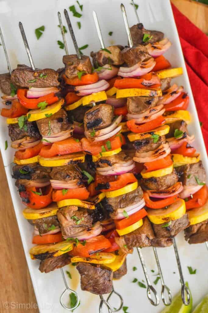 a pile of steak kabobs made with red peppers, yellow zucchini, and red onions with metal skewers on a white plate and garnished with parsley