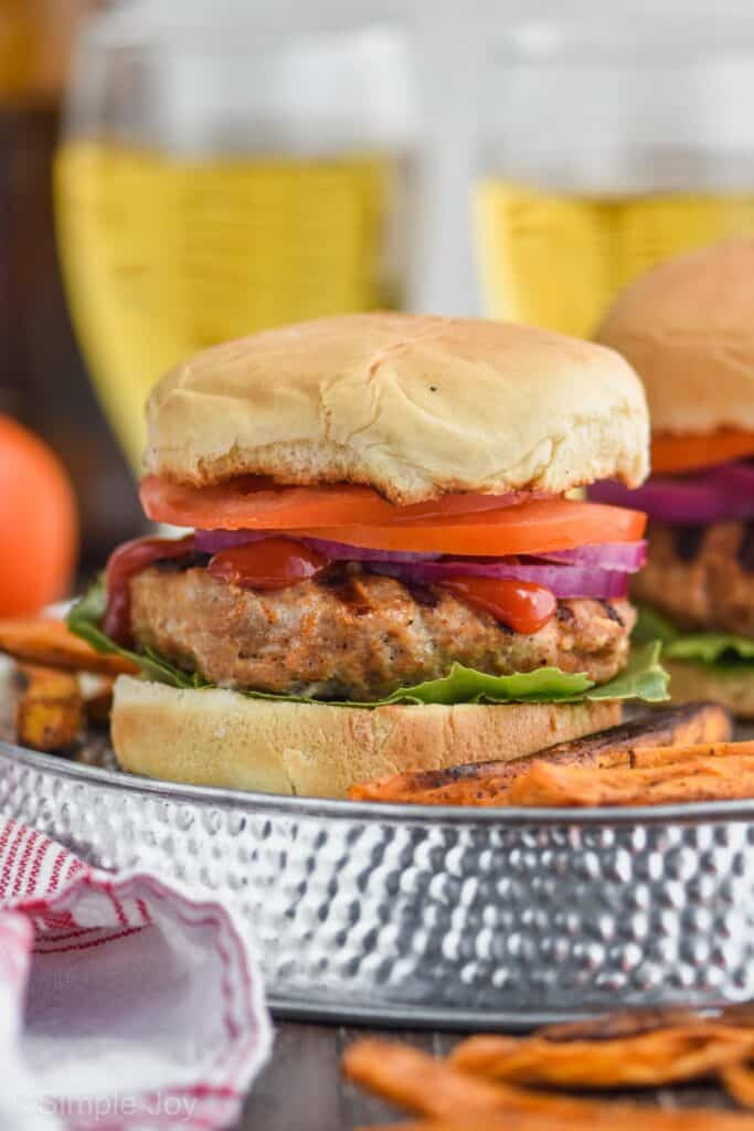 close up of a turkey burger on a bun with lettuce, ketchup, red onion, and tomato with sweet potato fries next to it