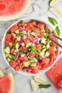overhead view of a white bowl with watermelon salad in it, full pieces of watermelon, lime wedges, and mint leaves around on the white countertop