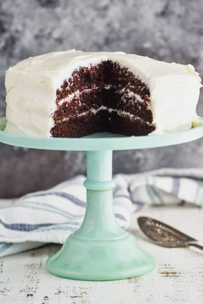 a three layer chocolate zucchini cake recipe on a teal cake stand with cream cheese frosting that has been cut into