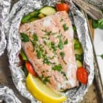 baked salmon in a foil packet garnished with flat leaf parsley and a fresh lemon wedge