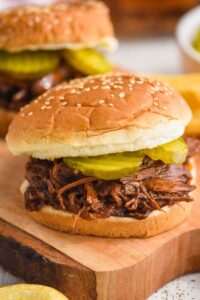 close up of bbq beef on a sesame seed bun with two pickles on it