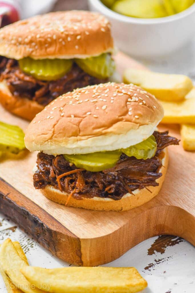 two crockpot bbq beef sandwiches on a cutting board, surrounded fries