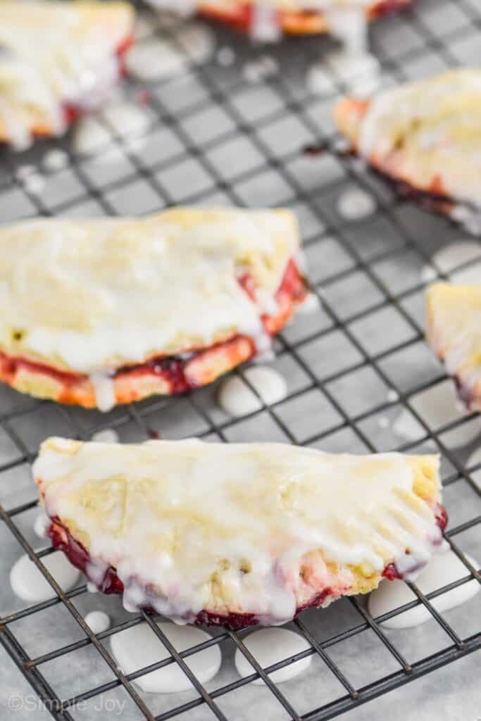 cherry hand pies on a cooling rack with glaze dripped over them