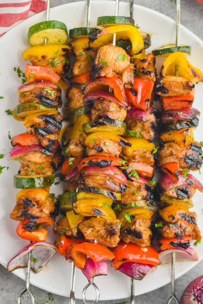 close up of grilled chicken kabobs on a plate