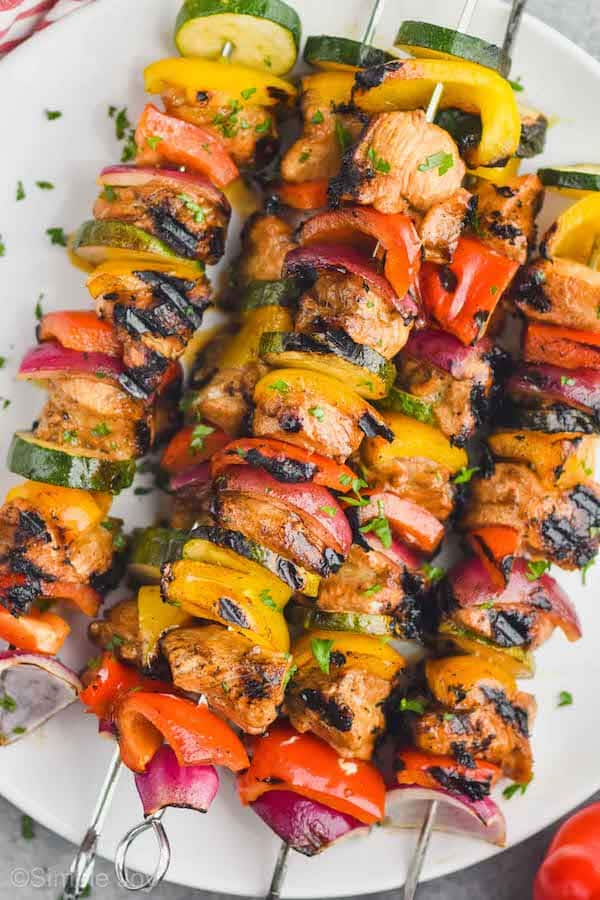 close up of chicken kabobs on a plate garnished with parsley