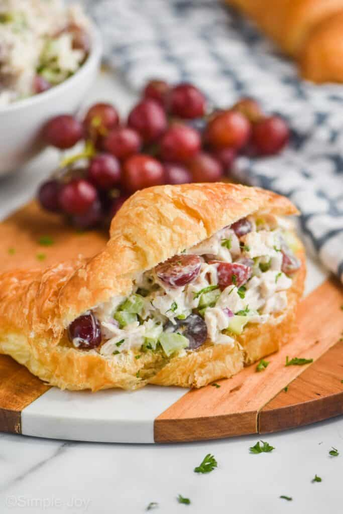 chicken salad sandwich on a croissant on a cutting board with grapes in the background