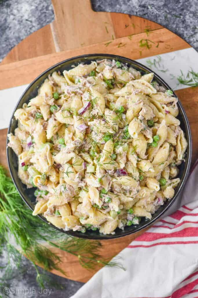 overhead photo of a serving bowl full of tuna pasta salad garnished with fresh dill with more fresh dill on the side