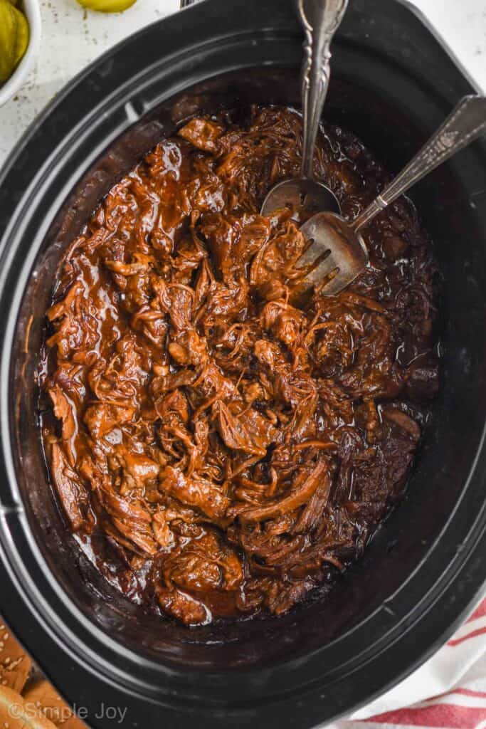 overhead of slow cooker bbq beef in a crockpot with a fork and spoon