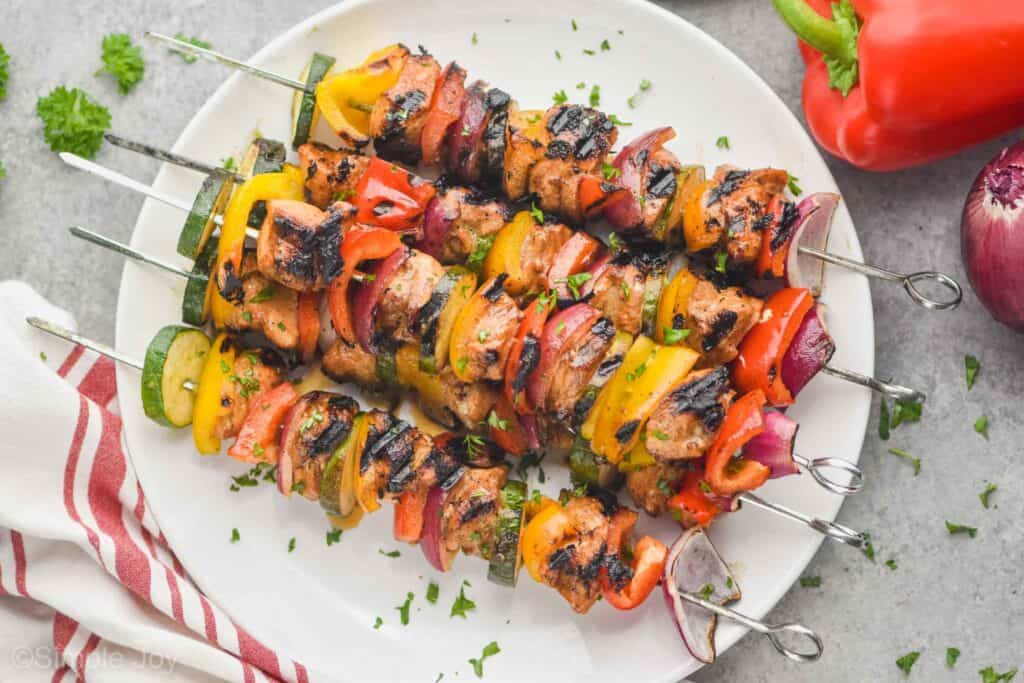 chicken kabobs that have been grilled and garnished with parsley, made with metal skewers on a white plate
