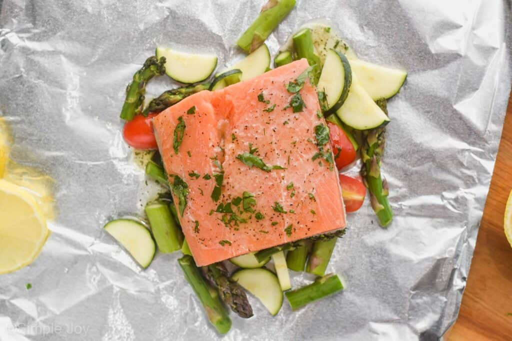 salmon prepared to be cooked in a foil packet with vegetables, toped with butter and parsley
