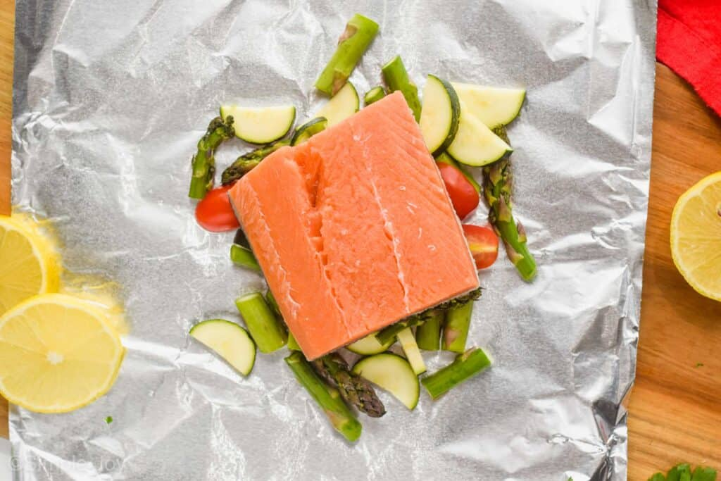 salmon prepared to be cooked in a foil packet with vegetables,