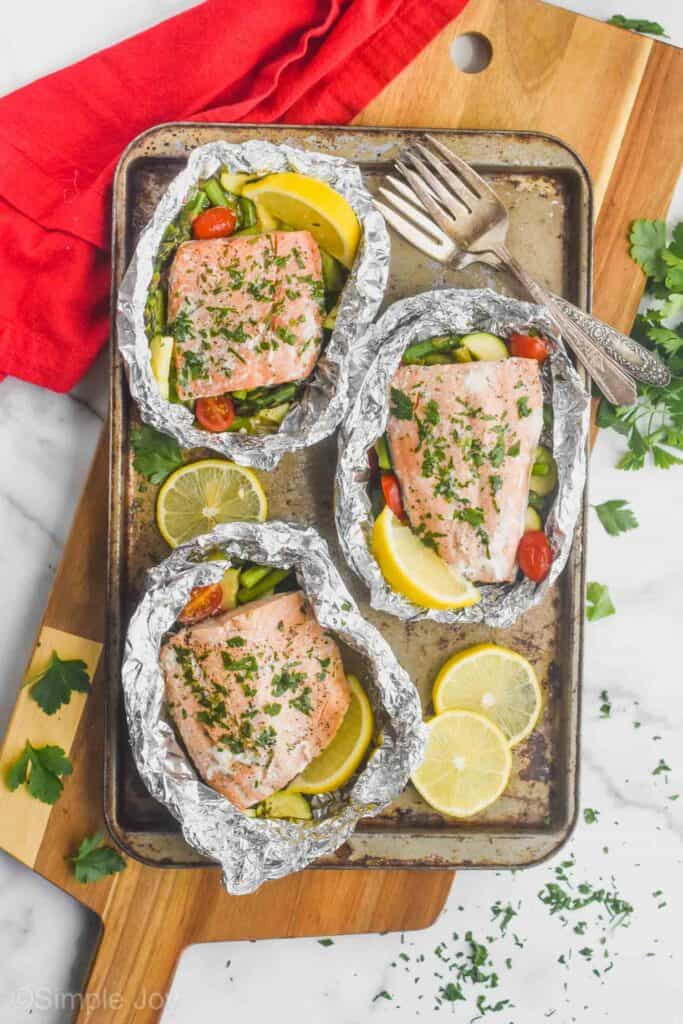 three salmon fillets in foil packets that were cooked with vegetables and garnished with parsley with fresh lemons around