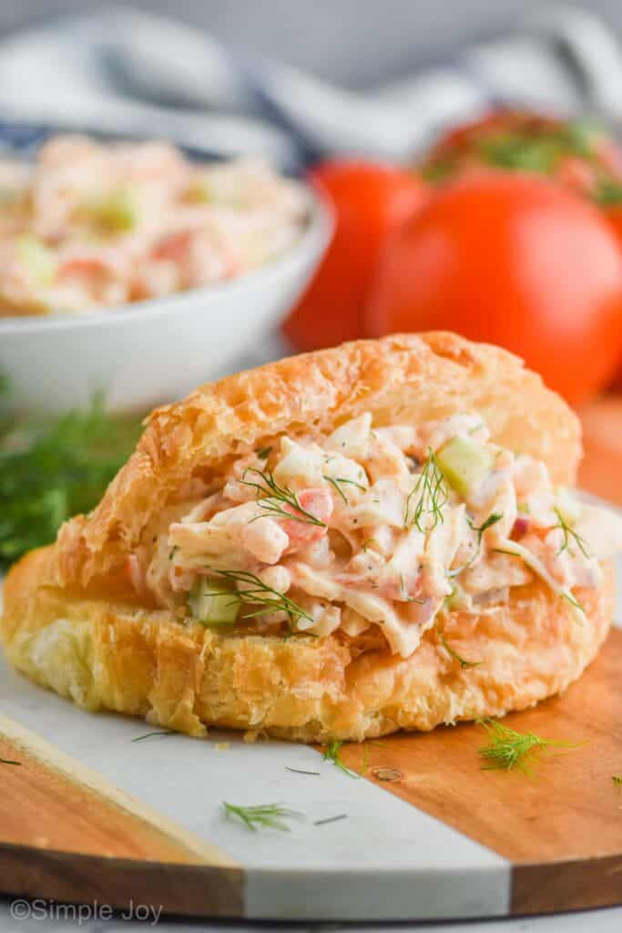 croissant sandwich with seafood salad on it, garnished with fresh dill, tomatoes in the background