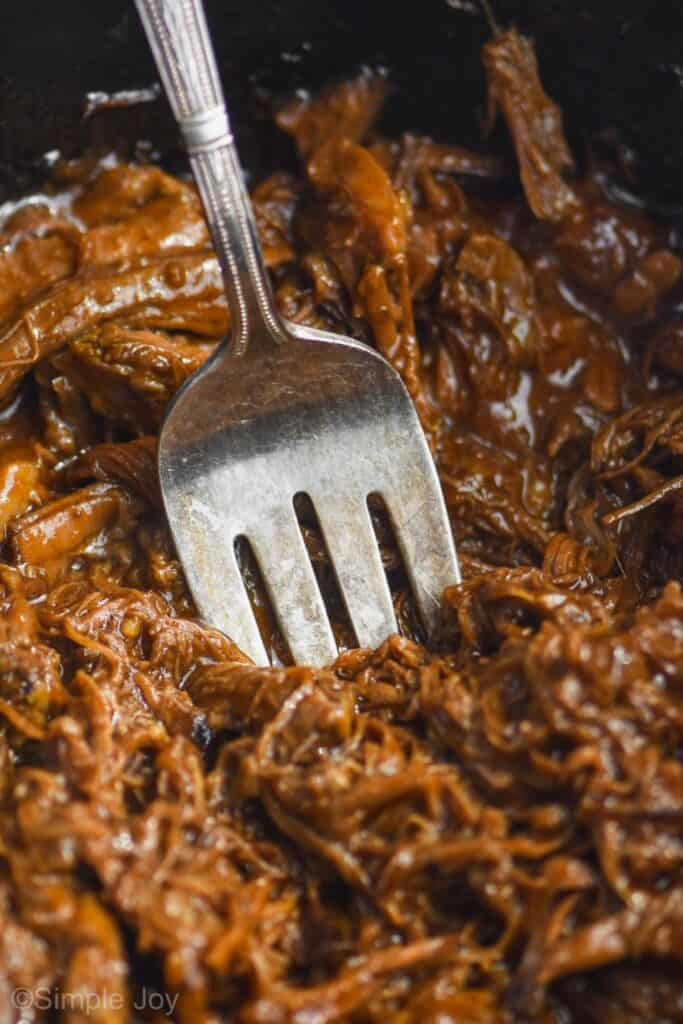 close up of a serving fork digging in to shredded bbq beef