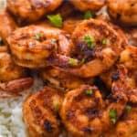 blackened shrimp recipe over white rice garnished with parsley bits