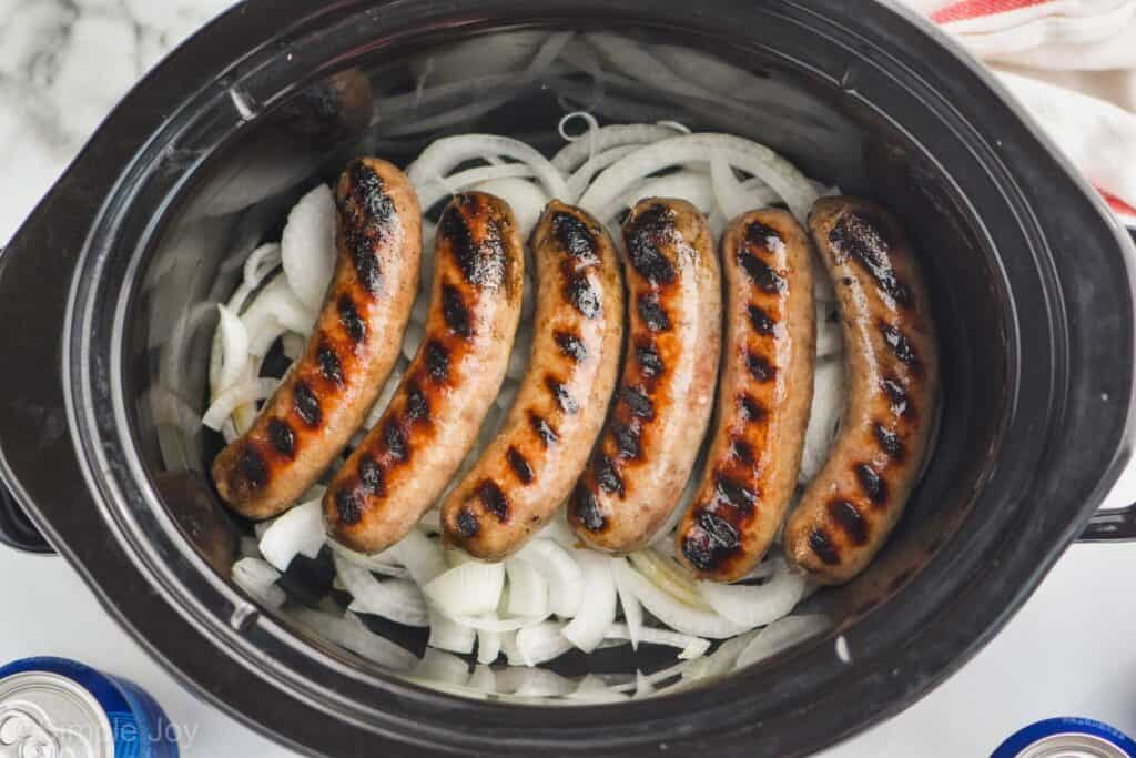 overhead of grilled brats a layer of onions in a slow cooker
