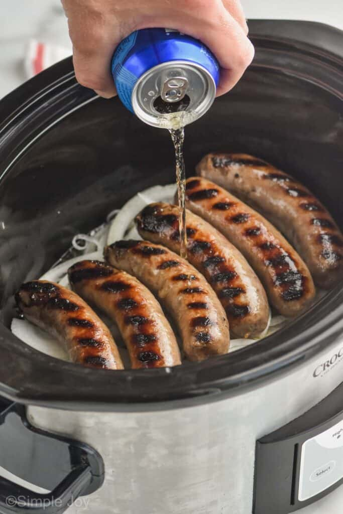 beer being poured over grilled brats with onions underneath in a layer in a slow cooker